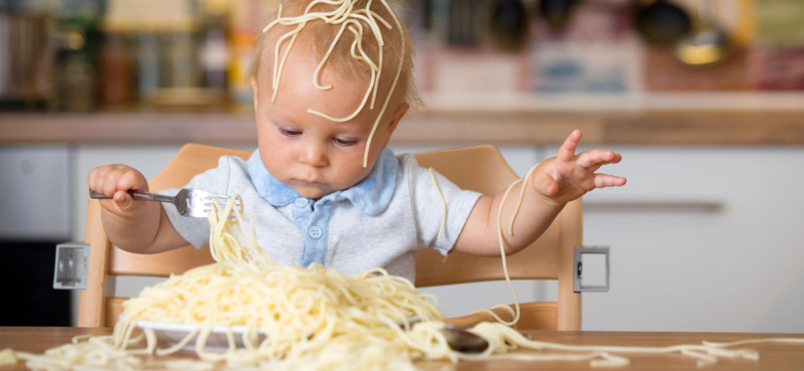 Little baby boy, toddler child, eating spaghetti for lunch and m